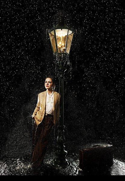 Frau an Gaslaterne im Regen